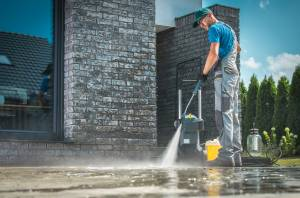 man pressure washing driveway